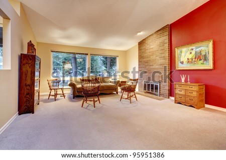 Large living room with red wall and brick fireplace.