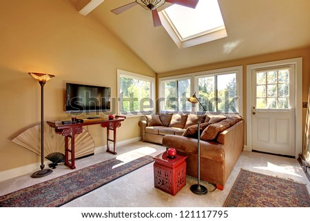 Large living room with sofa, TV and brown walls with beige carpet.