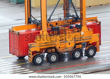 Large loader drives on wet asphalt and carries red container