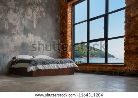 Large Loft Interior With Bed And Sea And Mountains In The Window