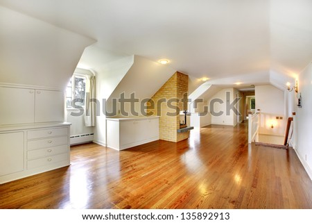 Large long attic room with fireplace. Empty with golden hardwood.