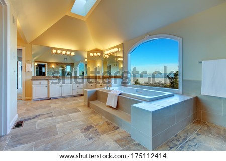 Large luxury bathroom with concrete floor, cathedral ceiling, whirlpool and arch window overlooking amazing mountain landscape