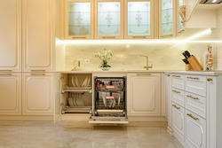 Large luxury beige and gold classic kitchen interior with furniture in Provence style, cabinet door and dishwasher are open