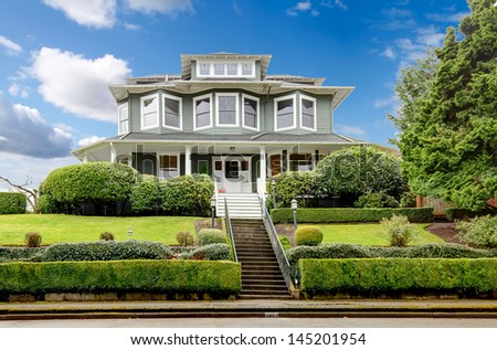 Large luxury green craftsman classic American house exterior.