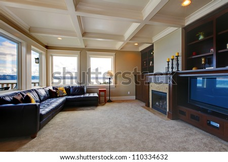 Large luxury living room with TV, water view, and shelves.