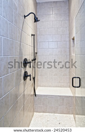 large luxury tile shower with pebble stone floor