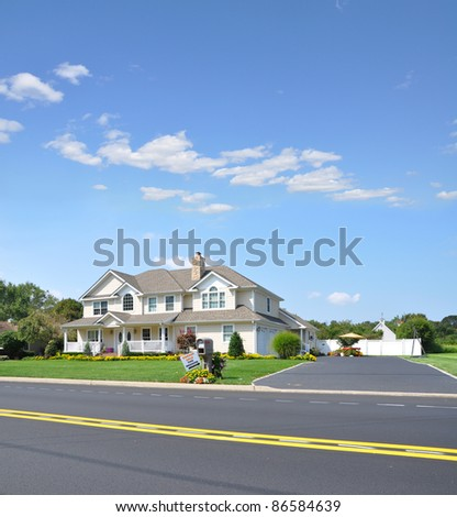 Large Luxury Two Car Garage Suburban McMansion style Home in Residential Neighborhood with Garage Sale Sign next to Mailbox on Sunny Blue Sky Day