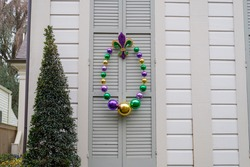 Large Mardi Gras (Fat Tuesday) beads and fleur de lis decorating shutters of home in New Orleans, LA, USA