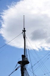 Large mast of an old wooden ship. A mast with an observation deck. Mast against the background of clouds.