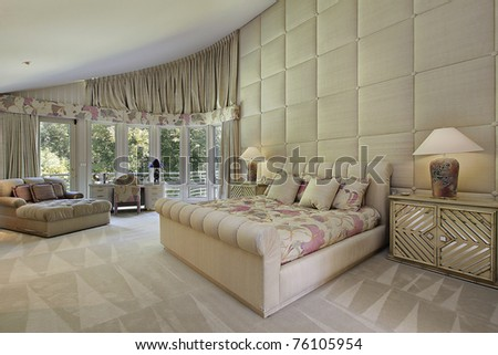 Large master bedroom in luxury home with doors to balcony