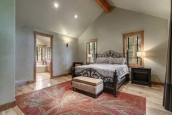 Large master Bedroom interior with grey plaster venetian wall finish and red rug on the floor. Luxury home with vaulted ceiling.