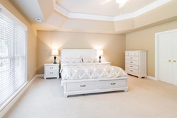 Large master bedroom with king sized bed and tribal print coverlet and pillows with warm gold colored walls and distressed white farm house style furniture