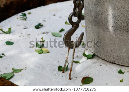 Large metal hook hooked on concrete structure #1377918275