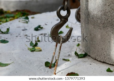 Large metal hook hooked on concrete structure #1379771393