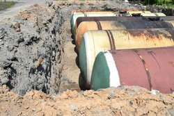 Large metal tanks are buried in the ground in the production warehouse.
