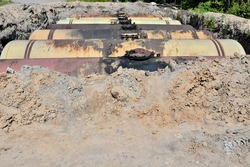 Large metal tanks are buried in the ground in the production warehouse