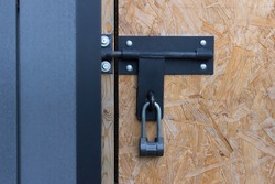 Large metallic padlock hanging on closed old fashioned door.