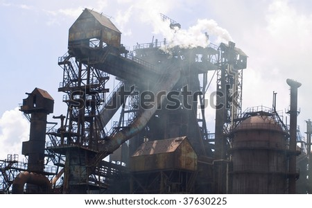 Large metallurgical plant blast furnace on a blue sky