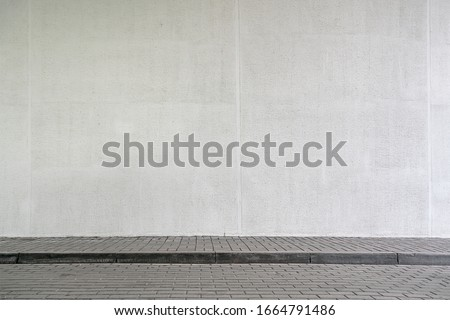 large modern building with high white wall near empty sidewalk covered with grey stone tiles on city street in spring
