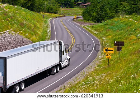 Large modern classic white truck with a trailer carrying commercial industrial cargo on the scenic highway winding among hills covered with trees and separated the safety barrier with road signs. #620341913