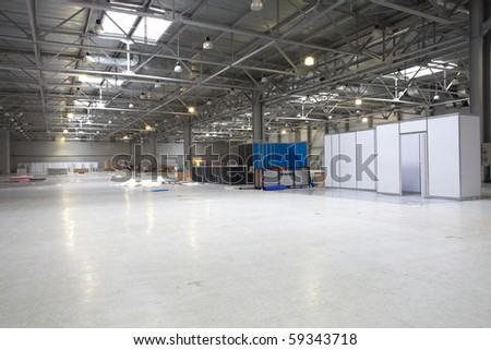 Large modern  exibition hall that unprepaired for exibition yet but already with some goods