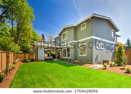Large modern grey new house with back porch from back yard with green grass and nice landscaping. Foto stock ©