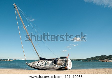 Large modern sailing yacht stranded on a beach after storms in the Mediterranean