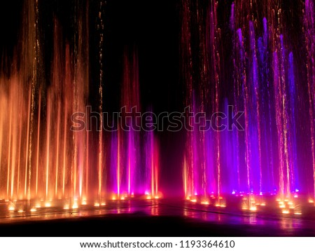 Large multi colored decorative dancing water jet led light fountain show at night