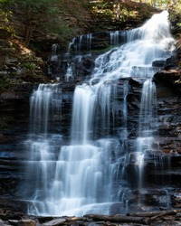 Large multi-tiered waterfall with silky cascades in Rickets Glen Pennsylvania