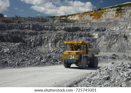 Large multi-toned mining truck in a limestone quarry on the background of blue sky with clouds. Quarry equipment. Mining industry. #725745001