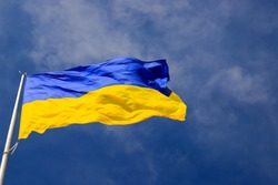 Large national flag of Ukraine  flies in the blue sky. Big yellow blue Ukrainian state banner in the Dnepr city, Dnepropetrovsk. Independence, flag, Constitution Day, National Holiday, text space