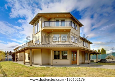 Large New luxury home exterior with balconies, three floors.