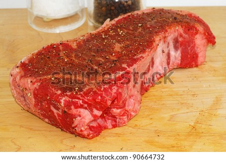 Large New York Strip Steak on wooden cutting board with salt, pepper and special seasoning being added prior to cooking.