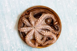 Large octopus tentacles on a wooden Board for Stripping on a blue background. Octopus on the kitchen table. Preparing to cook octopus