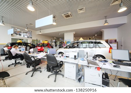 Large Office Of Shop Selling Cars. Office Workers Sit At Computers.
