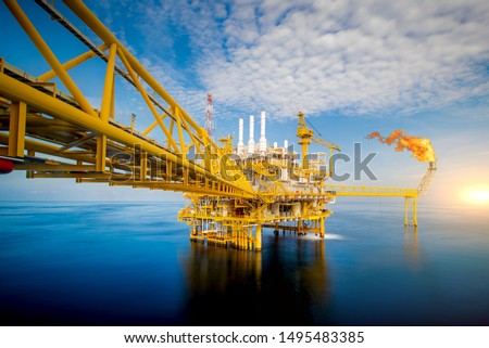 Large Offshore oil rig drilling platform at sunset and beautiful sky in the gulf of Thailand