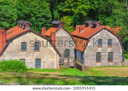 Large old abandoned factory building of a blacksmith and watermill #1005951415