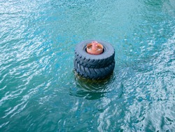 Large old black tires being used as bumpers at concrete dock, partially submerged in blue water.