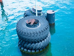 Large old black tires being used as bumpers at concrete dock, partially submerged in blue water