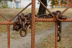 large old rusty iron chain on brown reinforcement bars