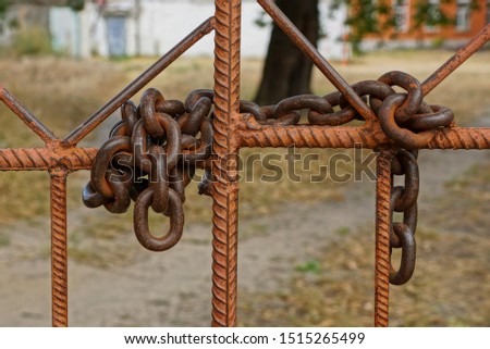 large old rusty iron chain on brown reinforcement bars stock photo