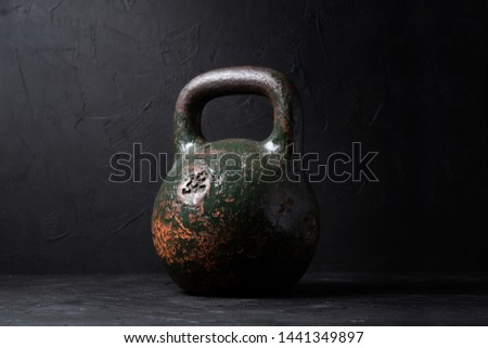 Large old sports weight of 32 kg on a dark background