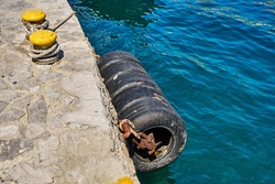 Large old tires of black colour hang on concrete pier edge to protect boats from impact above blue sea water with bright sunlight reflections on summer day