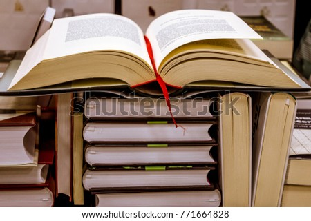 Large open book with red ribbon bookmark on a pile of various books. Reading a book in a library.