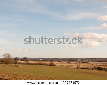 large open grass plain field with blue cloudy sky background nature; essex; england; uk