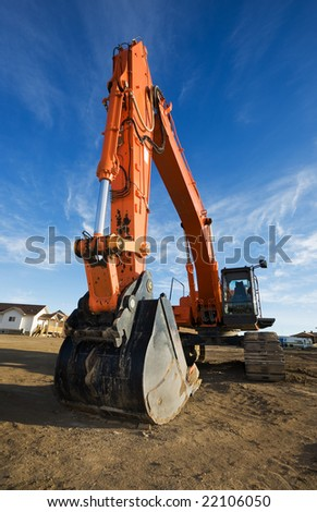 large orange backhoe at a construction site