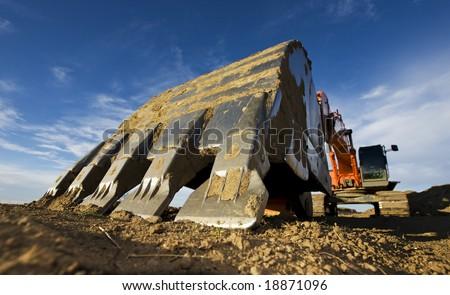 Large orange backhoe parked at a construction site