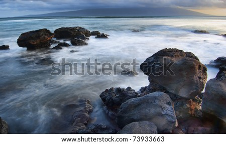 Large orange colored sea rocks with green waters and crashing beach waves