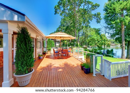 Large orange deck with umbrella and lake view.