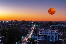 Large orange moon rising behind Sydney CBD buildings NSW Australia